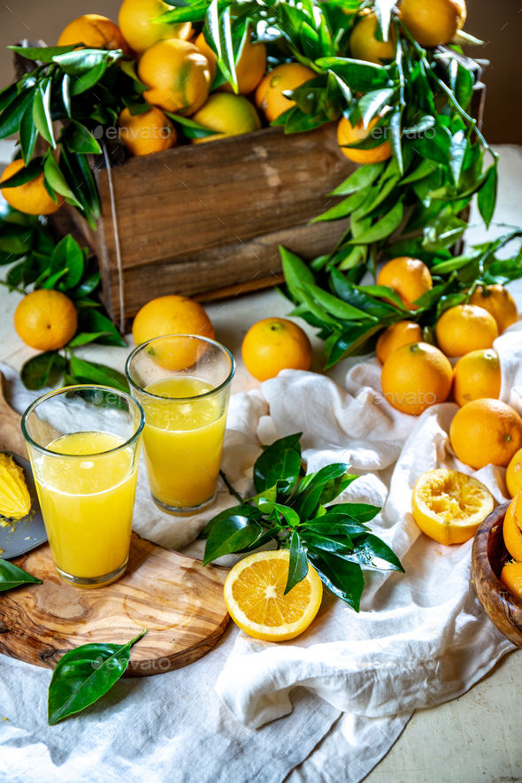 Box of orange fruit, with green leaves and orange juice on the table. Home gardening - Stock Photo - Images