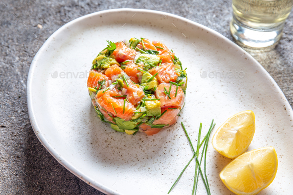 Peruvian nikkei food. Salmon avocado ceviche on black plate, black background top view - Stock Photo - Images