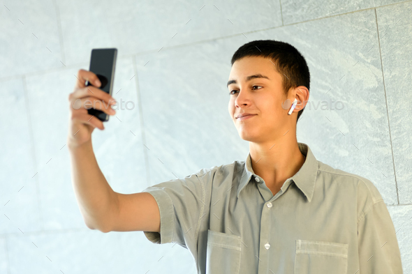 Young man wearing an earbud taking a selfie - Stock Photo - Images