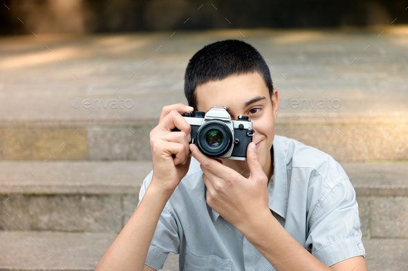 Young teenage boy photographing the viewer - Stock Photo - Images