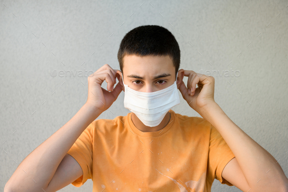 Young man putting on a surgical face mask - Stock Photo - Images