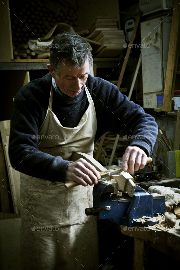 A man working in a furniture maker's workshop, sanding a piece of wood held in a clamp. - Stock Photo - Images