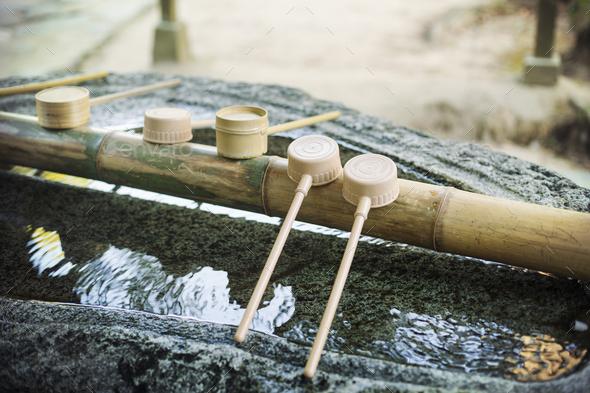 Close up of bamboo water hand washing basins at Shinto Sakurai Shrine, Fukuoka, Japan. - Stock Photo - Images