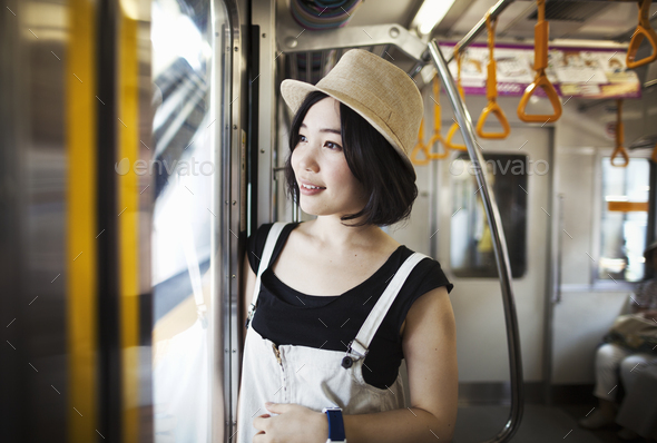Young woman wearing a hat traveling on a train. - Stock Photo - Images