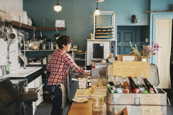 A woman working behind the counter in a coffee shop. - Stock Photo - Images
