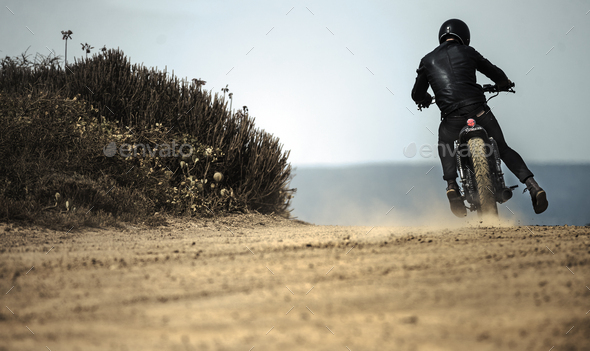 Rear view of man wearing crash helmet and black leathers riding cafe racer motorcycle on a dusty - Stock Photo - Images