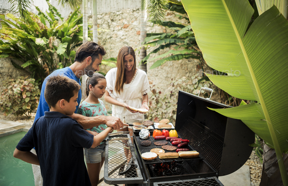 A family standing at a barbecue cooking food. - Stock Photo - Images