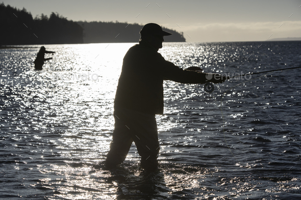 A silhouette of two fly fishermen standing in salt water while fly fishing for searun coastal - Stock Photo - Images