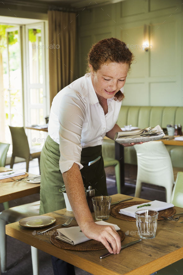 Woman wearing apron setting table in a restaurant. - Stock Photo - Images
