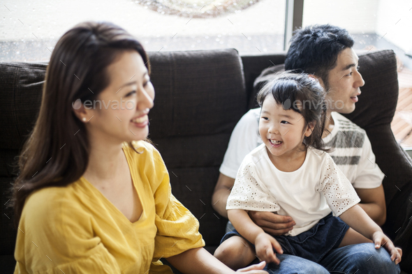 Portrait of smiling Japanese man, woman and young girl sitting on a sofa. - Stock Photo - Images