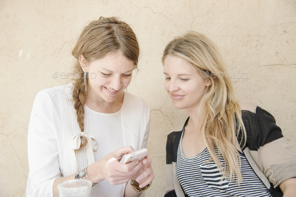 Two smiling women with long blond hair sitting at a table, looking at a cell phone. - Stock Photo - Images