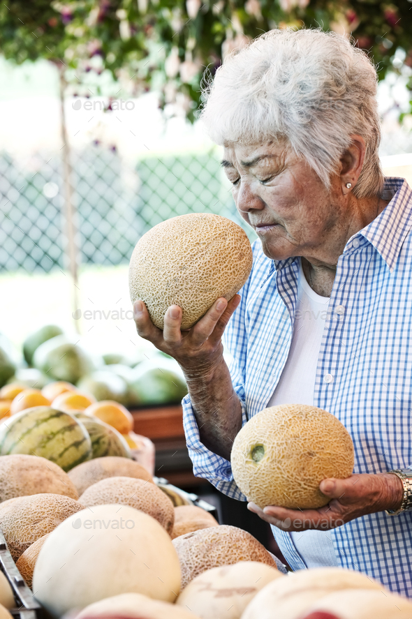 Senior woman standing at a farm stall, holding a fresh melon to her nose, smelling it. - Stock Photo - Images