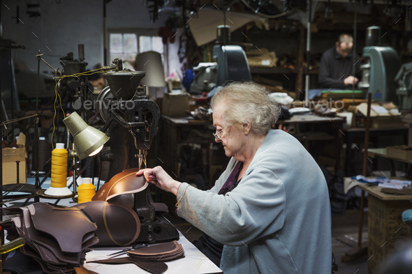 A grey haired senior worker, a woman sitting at a sewing machine in a shoemaker's workshop. - Stock Photo - Images