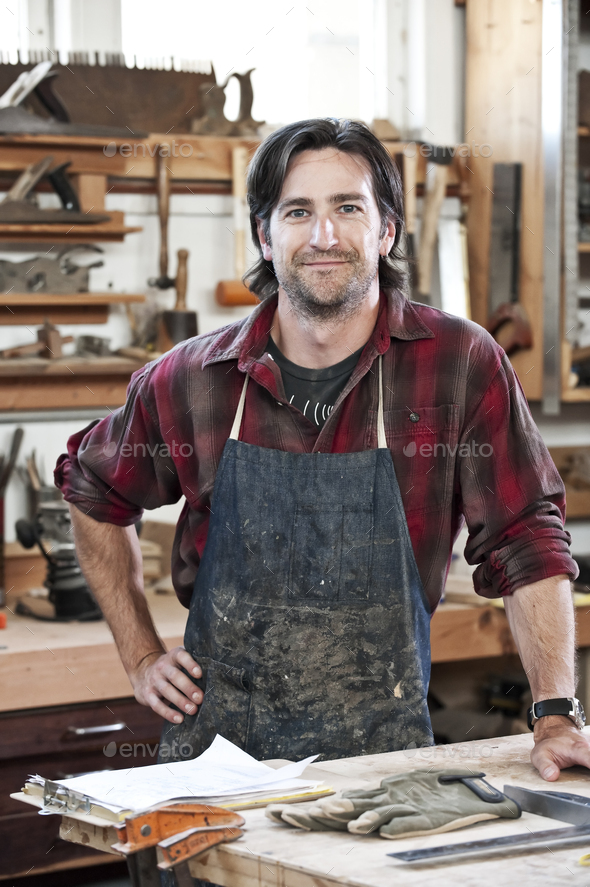 Caucasian man factory worker at a work station in a woodworking factory. - Stock Photo - Images