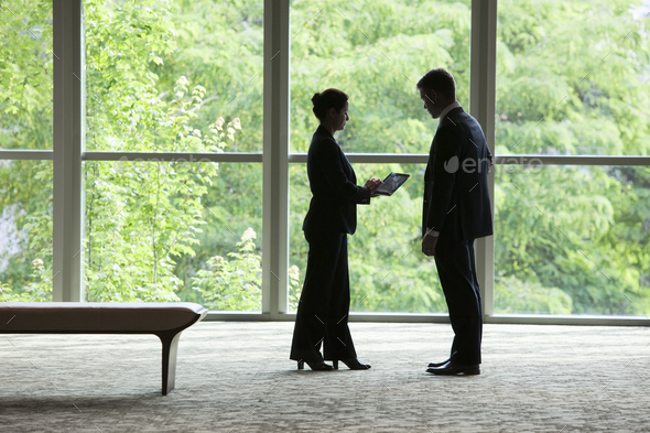 Caucasian businessman and woman looking at a computer notebook in front of a large window in a - Stock Photo - Images