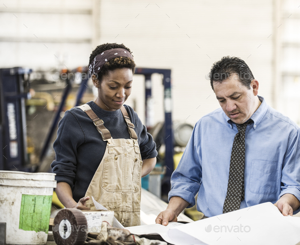 Hispanic man manager and black woman factory worker going over project plans in a sheet metal - Stock Photo - Images