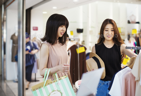 Two young women with long brown hair in a shopping centre. - Stock Photo - Images