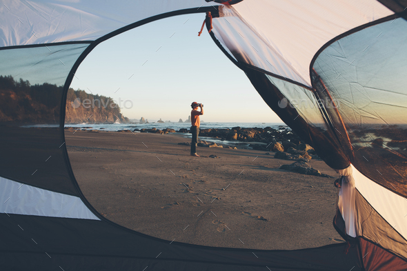 Man framed by camping tent, standing on beach and looking through binoculars at dusk, Olympic - Stock Photo - Images