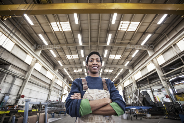 Black woman factory worker wearing coveralls in a large sheet metal factory. - Stock Photo - Images