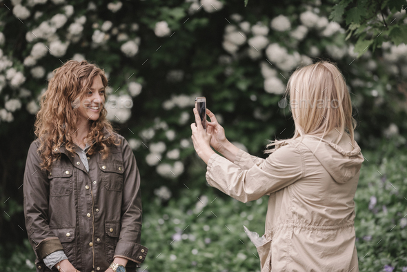 A woman taking a photograph with a smart phone of her companion on a country path. - Stock Photo - Images