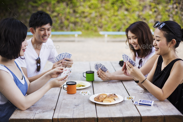 Three young women and a man sitting at a table, playing cards. - Stock Photo - Images