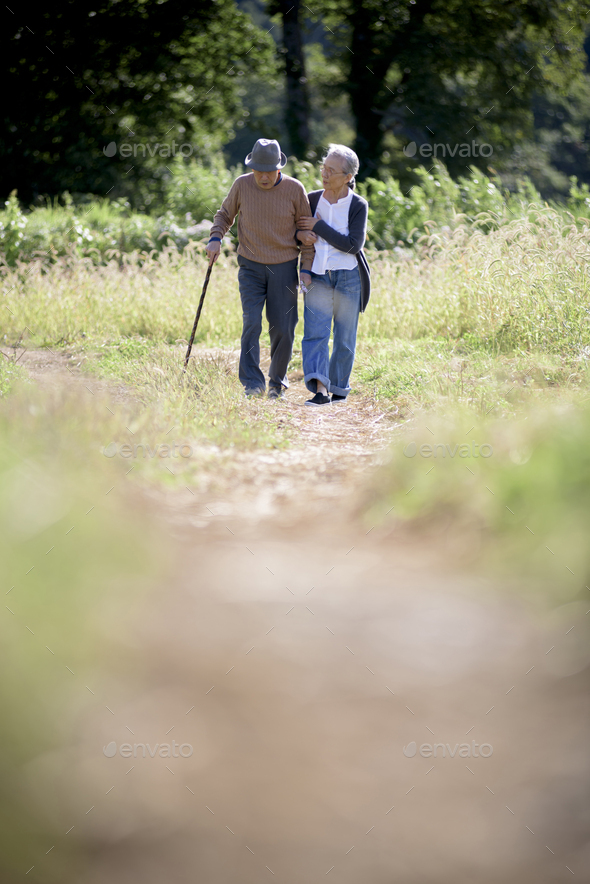 Husband and wife, elderly man wearing hat and using walking stick and elderly woman walking along - Stock Photo - Images