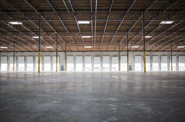 Wide angle interior view of largeempty warehouse and loading dock doors - Stock Photo - Images