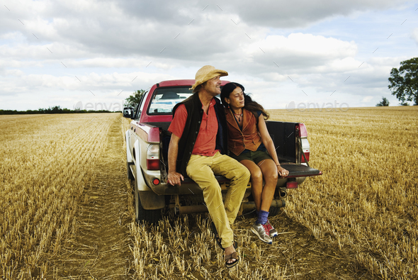A man in a straw hat and a woman sitting in the back of a pick up truck. - Stock Photo - Images