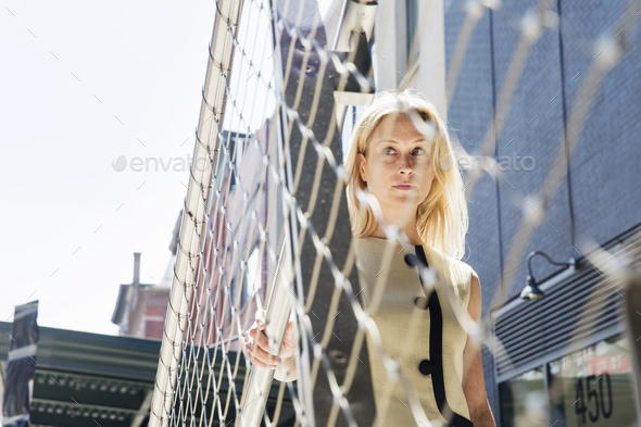 Businesswoman standing at a metal wire fence in New York. - Stock Photo - Images