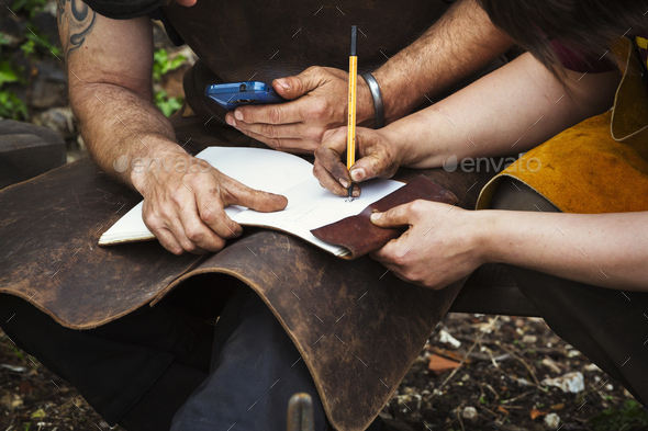 Two men wearing aprons writing into a notebook sat in a garden. - Stock Photo - Images