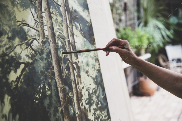 Close up of artist working on painting of trees in forest. - Stock Photo - Images