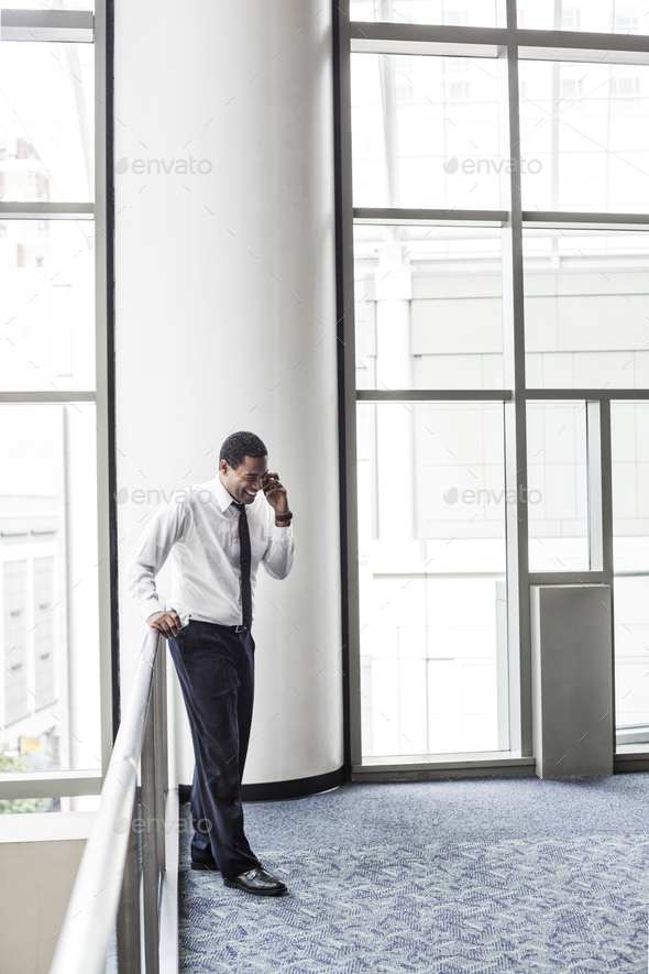 Black businessman on the phone in an office lobby. - Stock Photo - Images