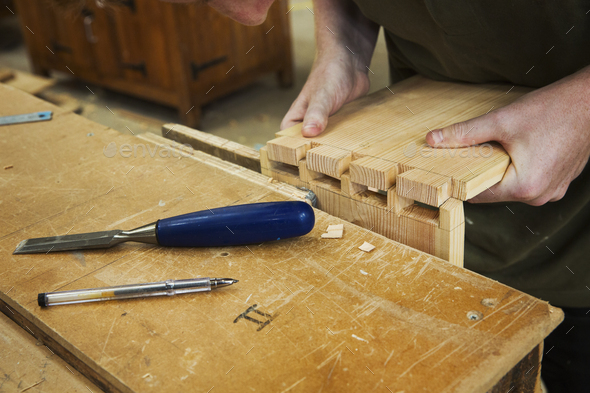 Close up of person working a boat-builder's workshop, joining together two pieces of wood. - Stock Photo - Images