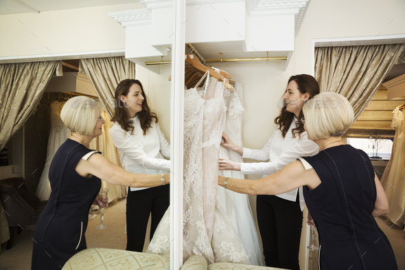 Two women, a client and retail advisor in a wedding dress shop, looking through the choice of gowns. - Stock Photo - Images