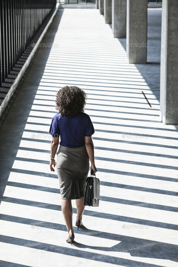 Businesswoman walking through large empty office space lit by the afternoon sun. - Stock Photo - Images