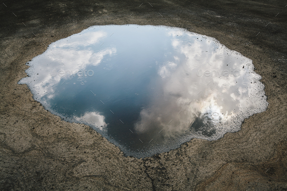Rain drops falling onto a large puddle. A reflection of sky and clouds. - Stock Photo - Images