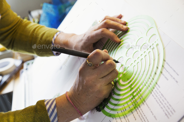 Close up of woman sitting at a drawing board, drawing with a fineliner, using a design template. - Stock Photo - Images