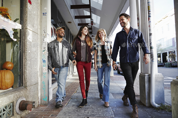 Two young men and two young women walking along a sidewalk, smiling. - Stock Photo - Images