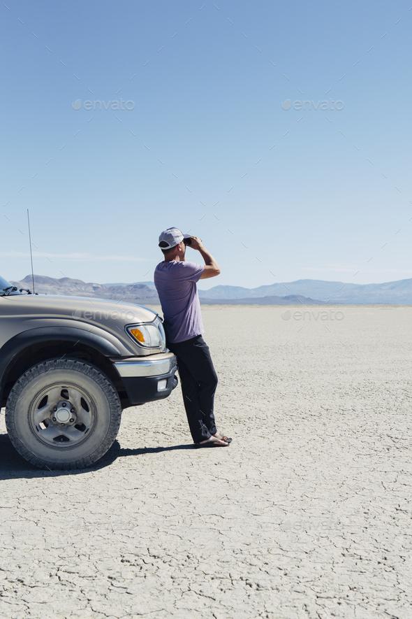 Man standing on vast desert, looking through binoculars and leaning against truck, Black Rock Desert - Stock Photo - Images