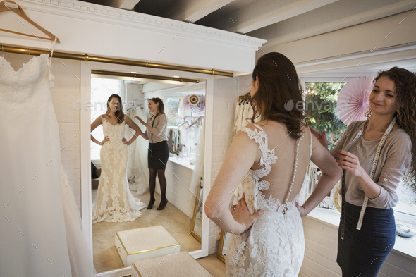A young woman in a full length white wedding dress, looking at her reflection in the mirror in a - Stock Photo - Images