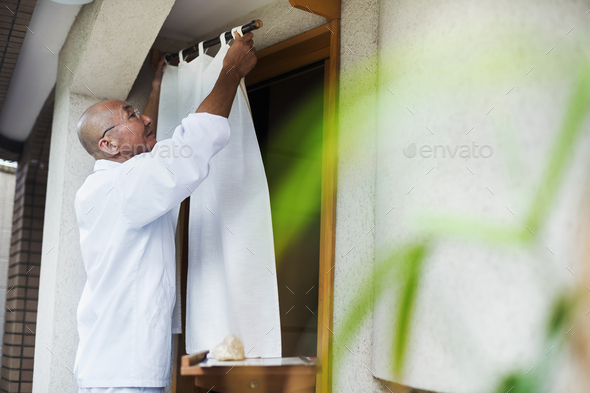 A chef in a small commercial kitchen, an itamae or master chef drawing a curtain across a door. - Stock Photo - Images
