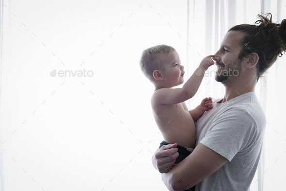 A young man holding a small child in his arms. - Stock Photo - Images