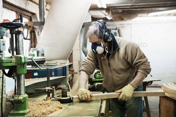 Man standing in a carpentry workshop, wearing a respirator and hearing protector, working on a piece - Stock Photo - Images