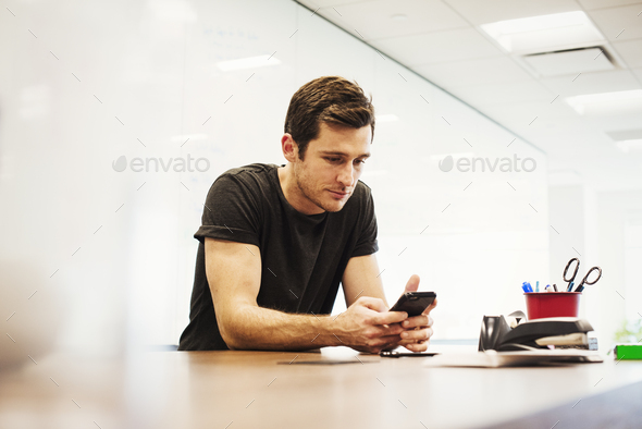 A young man sitting in a classroom leaning on a desk looking down at a cellphone. - Stock Photo - Images