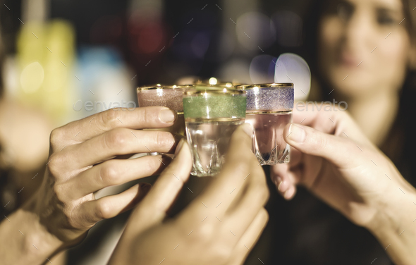 A group at a party holding shot glasses and celebrating. - Stock Photo - Images