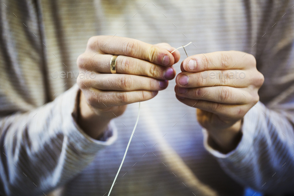 A craftsman's hands holding a leatherwork needle and threading cord through the eye of the needle. - Stock Photo - Images