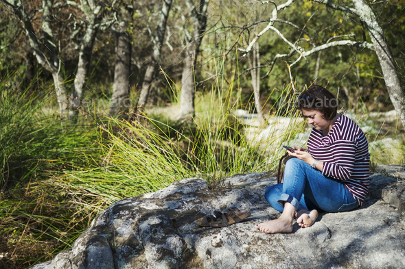 A woman sitting on the rocks in the shade by a river, looking at a smart phone. - Stock Photo - Images