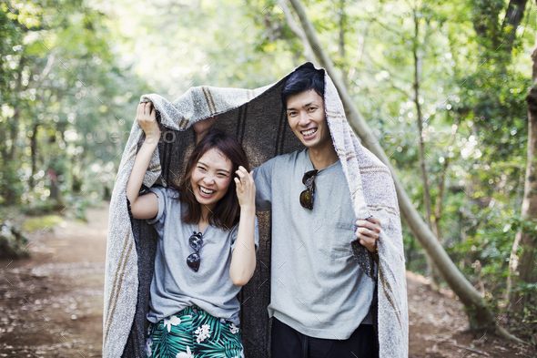 Young woman and man standing in a forest, holding a blanket over their heads. - Stock Photo - Images