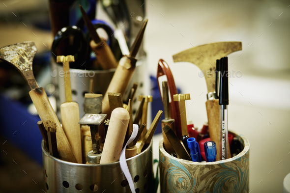 Metal pots full of hand tools for sklled work, for book binding tasks. - Stock Photo - Images