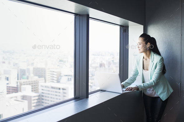 A business woman by a window with a view over the city, looking out. Laptop. - Stock Photo - Images